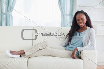 Woman sitting with legs on her sofa