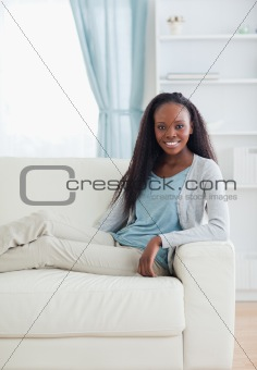 Smiling woman sitting with her legs on sofa
