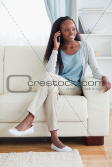 Woman with mobile phone on couch