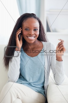 Close up of woman with mobile phone on the sofa