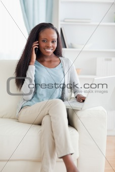Close up of woman with smartphone and laptop on the sofa