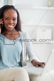 Close up of woman with cellphone and laptop on sofa