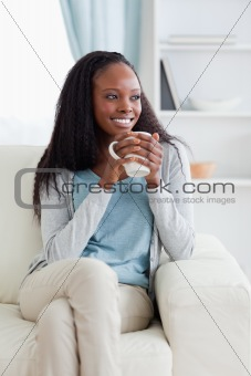 Woman on sofa with a cup