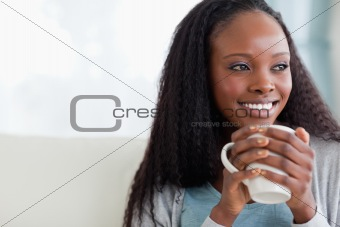 Close up of woman with a cup on sofa