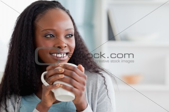 Close up of woman with a cup on couch