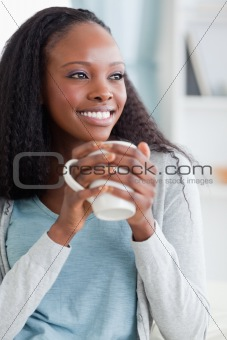 Close up of woman having a coffee on sofa