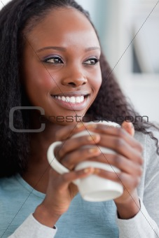 Close up of woman on sofa having coffee