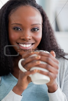 Close up of woman having coffee on couch
