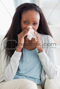 Close up of woman on couch blowing her nose