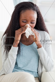 Close up of woman blowing her nose on sofa