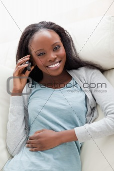 Close up of woman lying on couch with phone