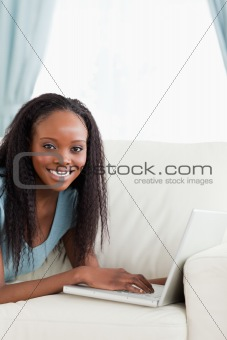 Close up of woman lying on the couch with her notebook