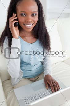 Close up of woman on the phone while using laptop