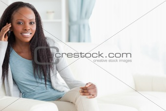 Woman sitting on sofa while using her phone