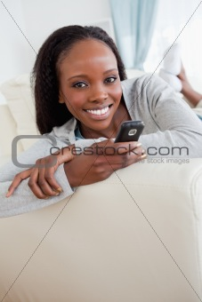 Close up of woman texting on couch