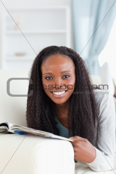 Close up of woman with booklet on sofa