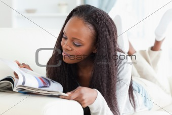 Woman looking at catalog on sofa
