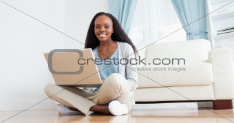 Woman sitting on the floor using her laptop