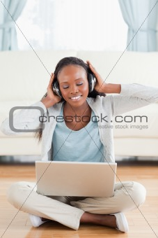 Close up of woman sitting on the floor listening to music