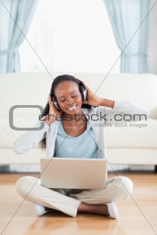 Close up of woman sitting on the floor enjoying music