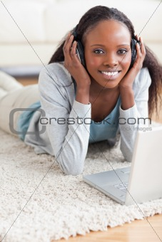 Close up of woman lying on the floor with her laptop listening to music