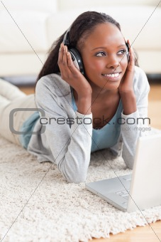 Close up of woman lying on the floor with her notebook listening to music