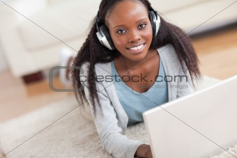 Close up of woman lying on the floor with her laptop enjoying music
