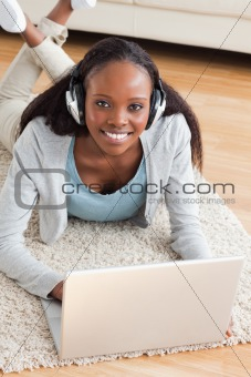 Close up of woman lying on the floor with notebook listening to music