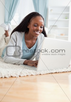 Close up of woman lying on the floor with her laptop