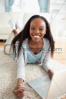 Close up of woman lying on the floor with her notebook shopping online