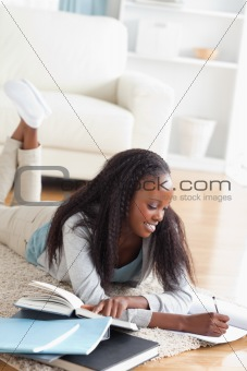 Woman lying on the floor taking notes