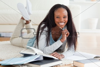 Female student lying on carpet doing homework