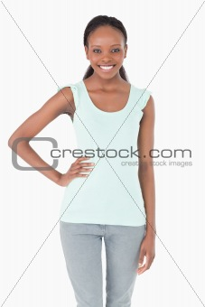 Close up of young woman with one arm akimbo on white background
