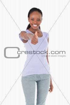 Close up of thumb up being given by woman on white background