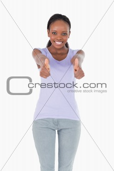 Close up of woman giving thumbs up on white background