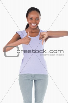 Close up of woman giving one thumb up and one down on white background