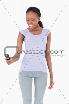 Close up of woman being surprised by text message on white background