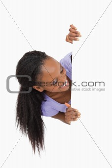 Young woman looking around the corner on white background