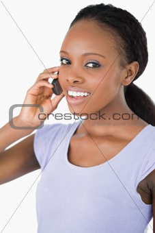 Close up of woman talking on the phone against a white background
