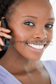 Close up of woman talking on the mobile phone against a white background