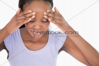 Close up of woman rubbing her temples against a white background