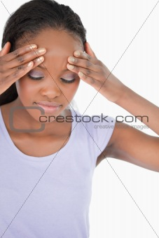 Close up of woman experiencing a headache on white background