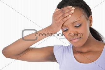 Close up of woman holding her forehead against white background