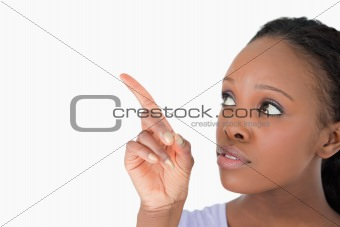 Close up of woman pointing at something next to her on a white background