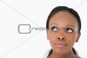 Close up of woman's face looking upwards diagonally on white background