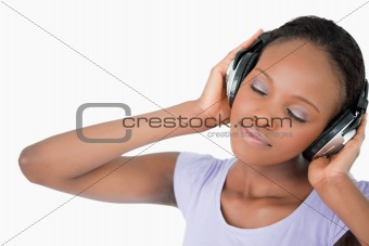 Close up of woman with headphones against a white background