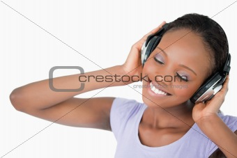 Close up of woman listening to music against a white background