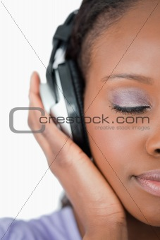 Close up of woman enjoying music against a white background