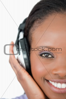 Close up of young woman with headphones on white background