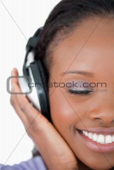 Close up of young woman listening to music on white background